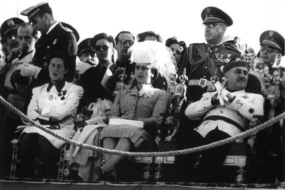 Franco y su esposa, presidiendo un acto rodeados de cortesanos.