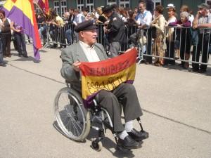 Francisco Ortiz desfila en Mauthausen en 2009 con la bandera republicana que guardó en el barracón.