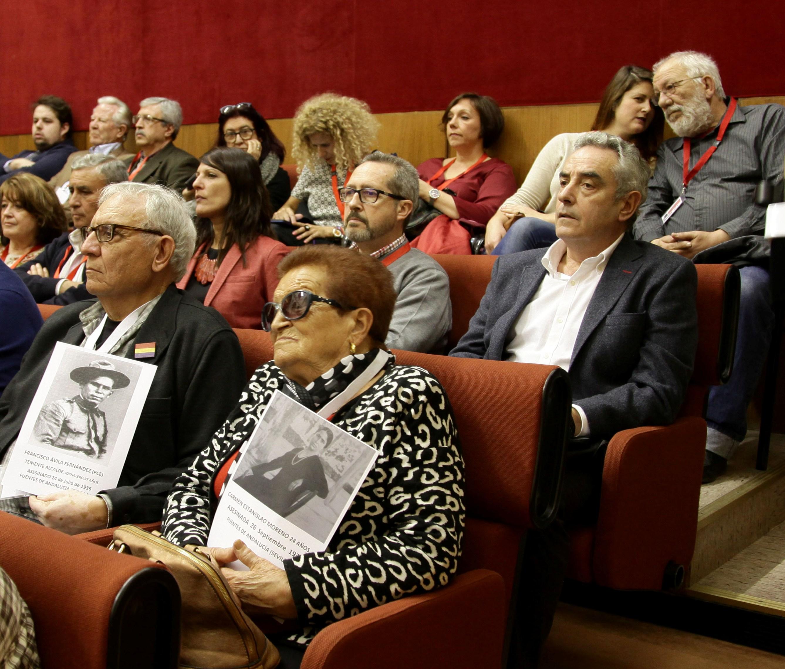 Virtudes Ávila mostrando la foto de sus padres, junto a Juan Morillo, en el Parlamento andaluz.